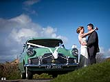 Couple share a moment beside their beautiful vintage wedding car at Charles Fort  before going to Acton's Kinsale, for their reception.