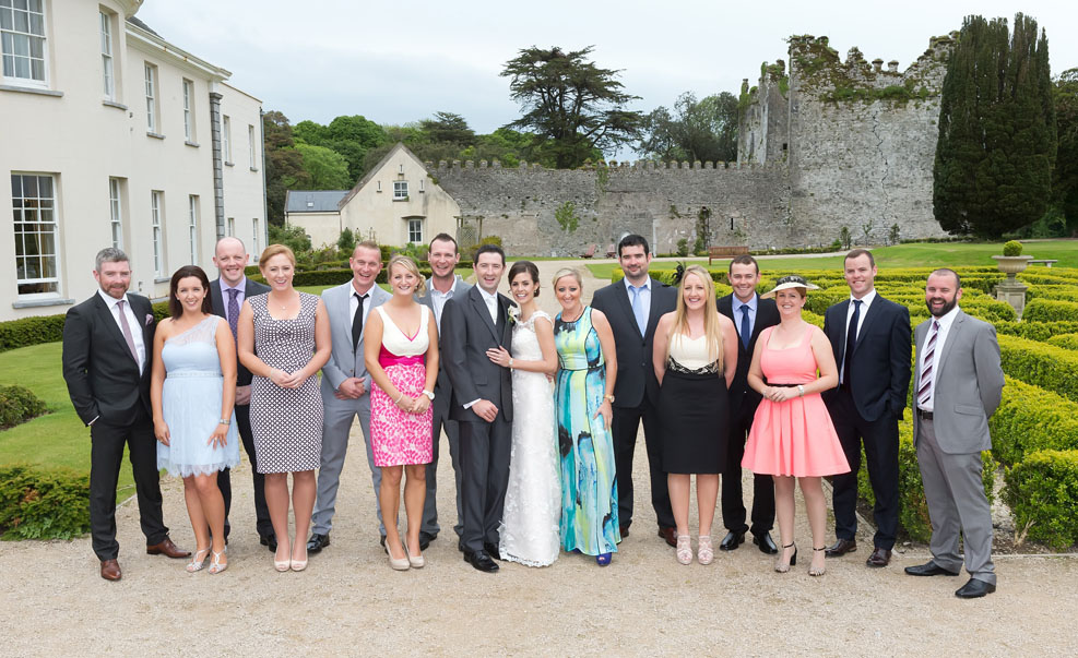 Bride and groom posing for their wedding portraits, with their friends at Castlemartyr Resort, Co. Cork, Ireland.