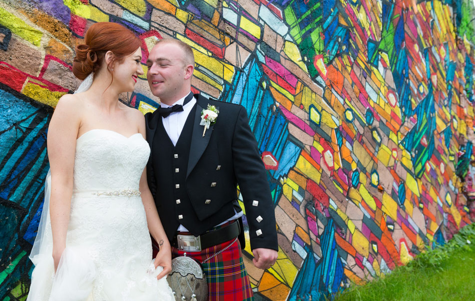 Wedding couple pose against an artist's painted wall in the city of culture, Limerick, Ireland