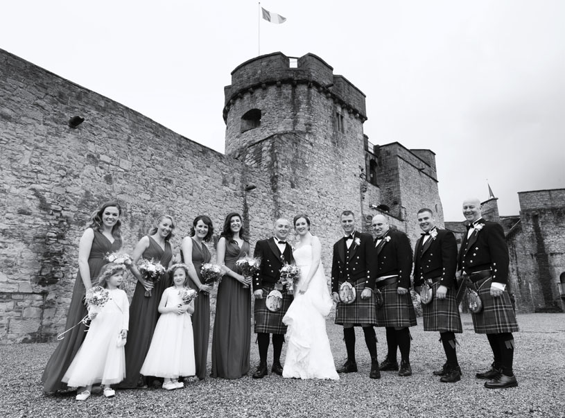 Black and white portrait of bridal party after the wedding on the grounds of King John's castle, Limerick, Ireland.