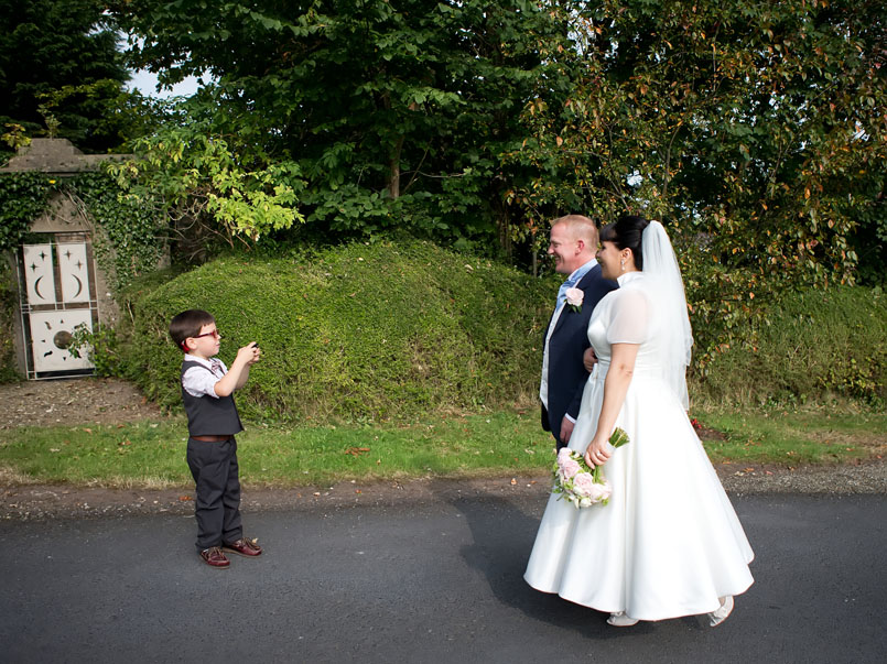 Cute little boy takes a photograph of a wedding couple on their wedding day at the Mustard Seed, Ballingarry, Co. Limerick.