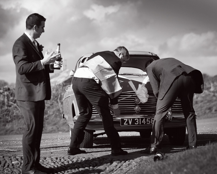 Groomsmen trying to fix the ribbons on the wedding car, Kinsale, Co. Cork, Ireland.