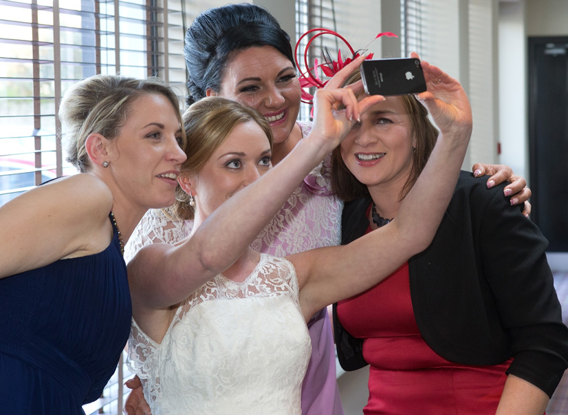 Bride takeing a few selfies with friends at her wedding in Acton's hotel, Kinsale, Co. Cork.